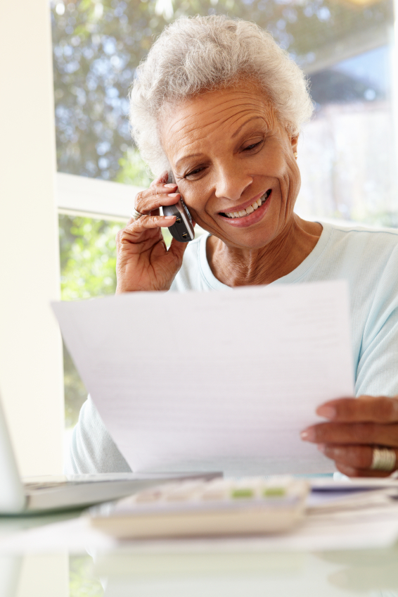 Senior Woman On Phone Using Laptop At Home